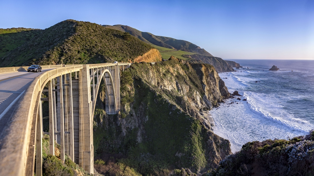 scenic view of california freeway next to the ocean with car