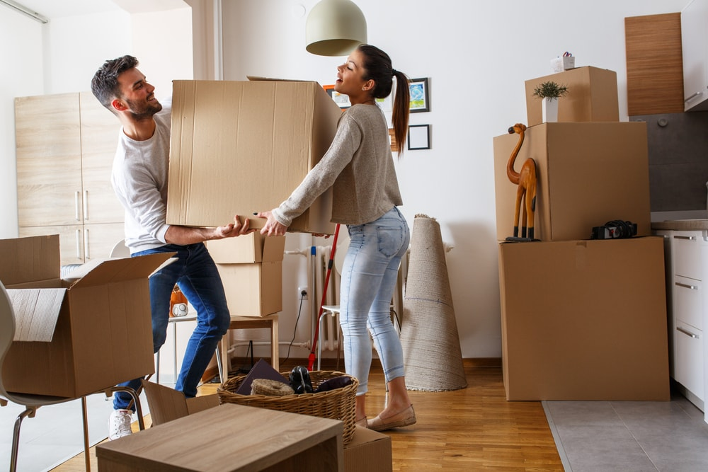 Young couple carrying big cardboard box at new home