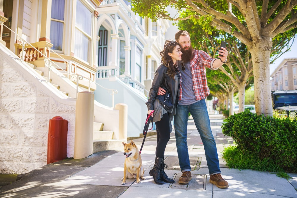 couple taking photo at painted ladies san francisco with shiba inu on leash